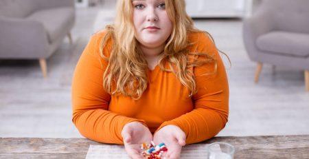 tučná žena držiaca lieky v rukách